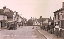 Broad Street, Boxford. The White Hart has been painted showing Tudor beams on the upper levels. C. Stanley's shop has a C.E. Sissons of Hadleigh fish van outside. The road is just dirt. Turners name on what is now the Coffee Box.