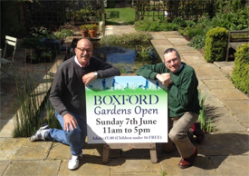 Getting the message across! John Kirby and Joe Barrett by their pond - with a board advertising the open gardens day